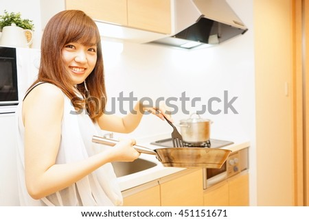 Young Japanese woman cooking foods in a kitchen
