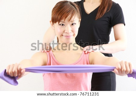 young Japanese woman doing stretch bands exercise - stock photo