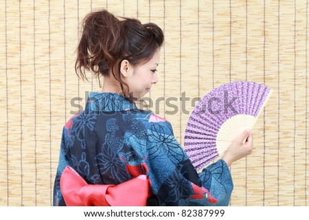 Young japanese woman in traditional clothes of kimono with japanese fan