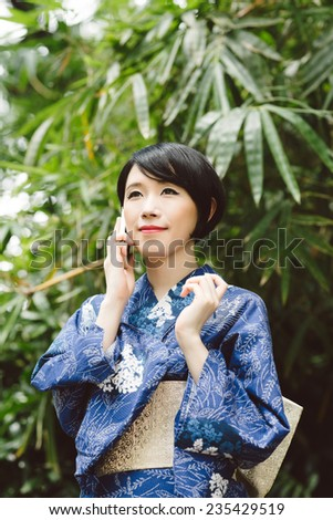 Young Japanese woman in traditional kimono talking on the phone - stock photo
