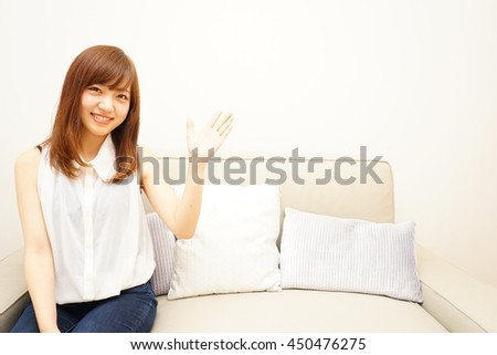 Young Japanese woman pointing something with smile - stock photo