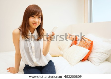 Young Japanese woman using smart phone on her bed - stock photo