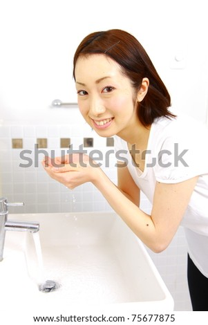 young Japanese woman washes her face in lavatory