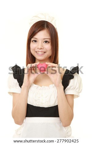 young Japanese woman wearing french maid costume with pink heart - stock photo