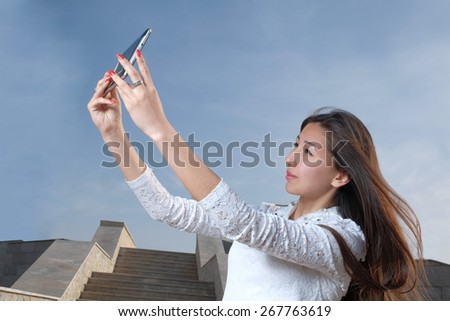 Young japanese women with long hair do selfie in city park afainst steps and clear blue sky with light haze, copyspace on the sky - stock photo