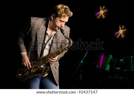 Young jazz musician with saxophone. In the background, music drums kit. - stock photo
