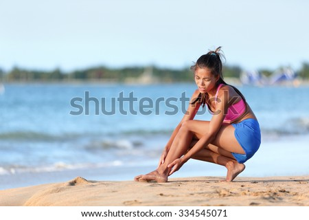 Young jogger running suffering from ankle pain injury on beach. Full length of female runner in sportswear. Woman is holding her twisted leg while crouching on sea shore. - stock photo