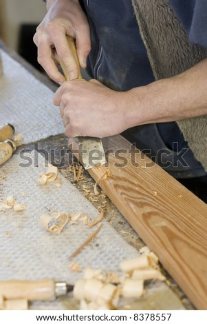 Young joiner making furniture in his manufactory - stock photo