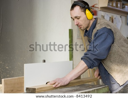Young joiner making furniture in his manufactory. - stock photo