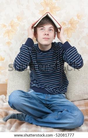 young joy boy readig book on sofa at home - stock photo