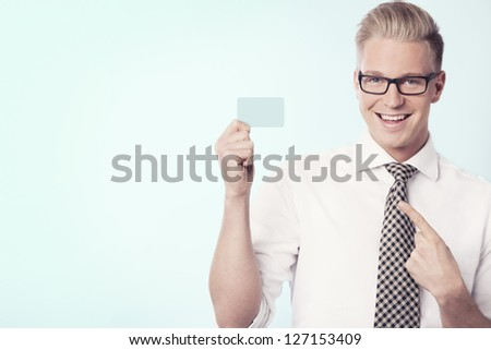Young joyful businessman pointing finger at empty business card with space for text while holding it, isolated. - stock photo