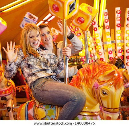 Young joyful couple visiting an attractions park and waving at camera while on a carousel ride during a fun night out together. - stock photo