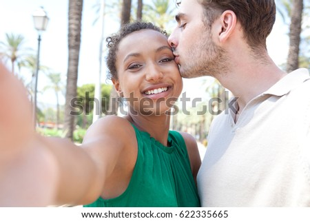 Young joyful ethnically diverse couple kissing, sightseeing destination on holiday, holding camera taking selfies photos smiling looking, networking outdoors. Travel technology lifestyle, recreation.