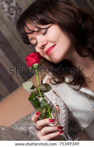 Young joyful girl with a red rose