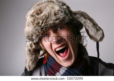 Young joyful man in winter clothes - stock photo