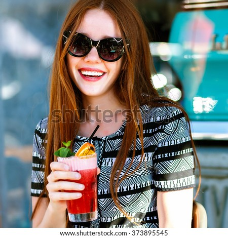 Young joyful smiling girl having fun at  outdoor city cafe terrace, screaming , relaxing day with friends, elegant glamour ginger girl, cute emotions, travel, vacation, drinking bright lemonade.