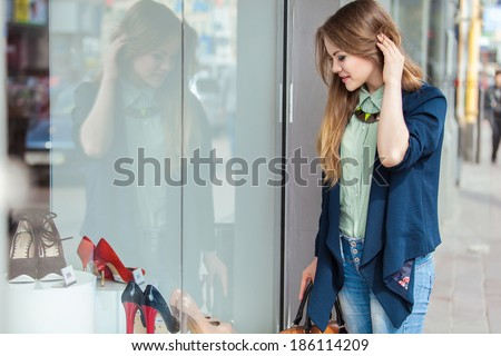 Young joyful woman looking at the shop window - stock photo
