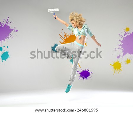 Young joyful woman with a paint roll - stock photo
