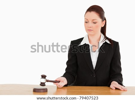 Young judge knocking a gavel against a white background - stock photo