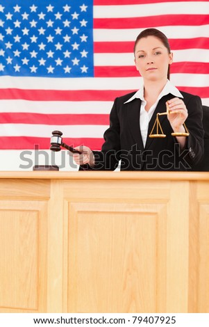 Young judge knocking a gavel and holding scales of justice with an American flag in the background - stock photo
