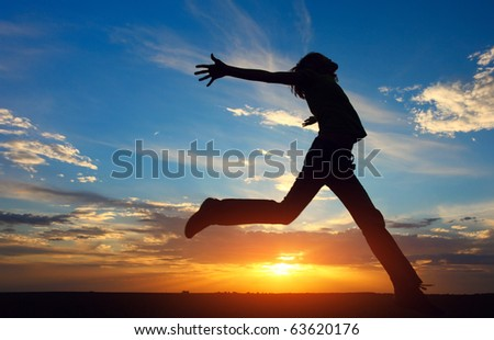 Young jumping woman with raised hands on sunset - stock photo
