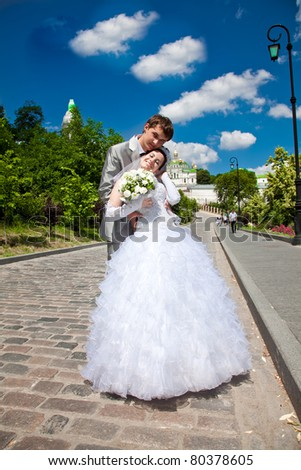 Young just married couple hugging outside. - stock photo