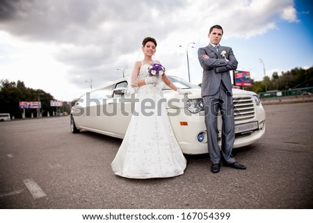 Young just married couple standing against long white limousine - stock photo