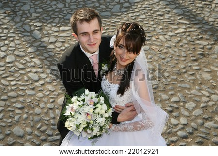 Young just married smilling couple agains road from bricks