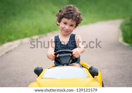 Young kid close up portrait with toy car outdoors. - stock photo