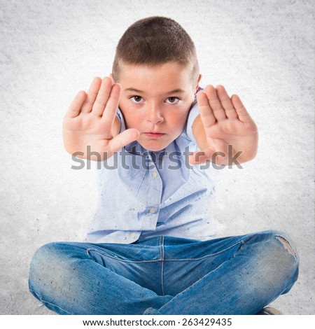 Young kid doing stop sign over textured background  - stock photo