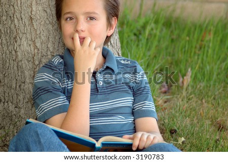 Young kid enjoying his summer reading. - stock photo