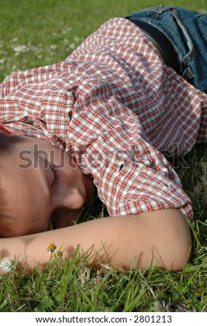 Young kid falling asleep in a spring meadow - stock photo