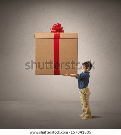 Young kid holding a big Christmas present - stock photo