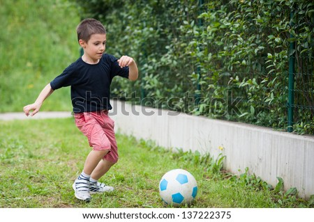 Young kid playing soccer. - stock photo