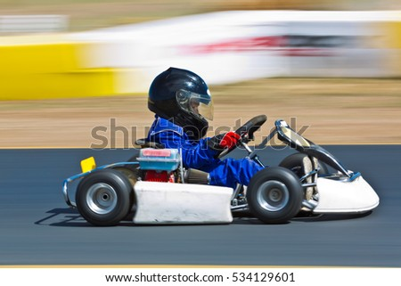 Young Kid Racing A Go Cart Around Track Panned To Show Speed