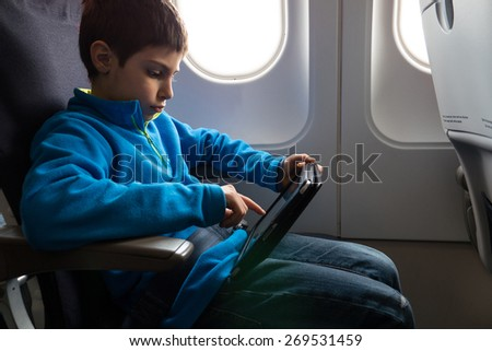Young kid relaxing using tablet inside airplane. - stock photo