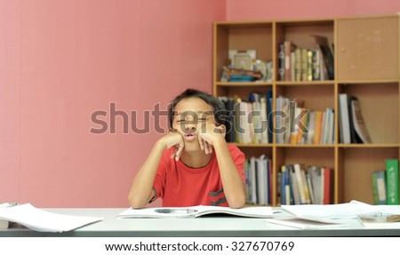 young kid shows bored face during studying  - stock photo