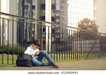 Young kid sitting outdoors - stock photo