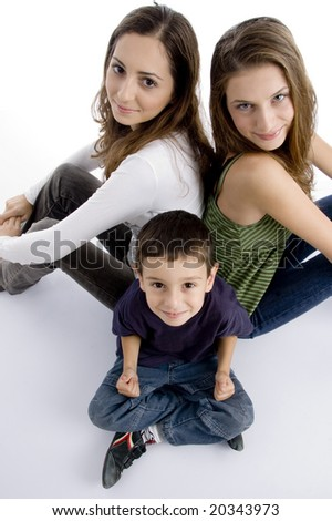 young kid sitting with teenagers and facing at camera all, on an isolated white background - stock photo