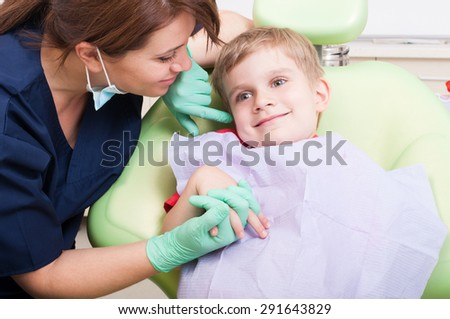 Young kid smiling in dental office with beautiful and friendly woman dentist doctor