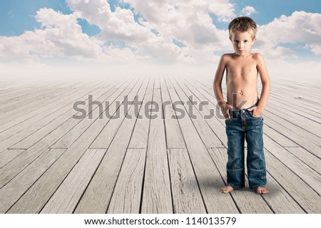 Young kid standing on a wood floor with cloudy blue sky. - stock photo