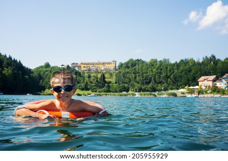Young kid swimming in Lavarone lake with life buoy. Trentino Alto Adige region, Italy.
