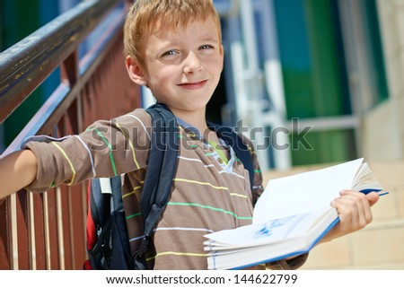 Young kid with book in front of school building - stock photo