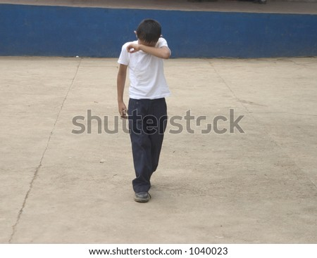 Young kid with his hand over his face like he is embarassed or dejected (some noise) - stock photo