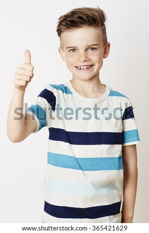 Young kid with thumbs up, portrait - stock photo