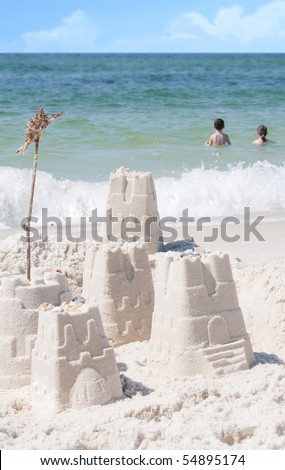 Young kids having fun in gorgeous ocean by sand castles - stock photo