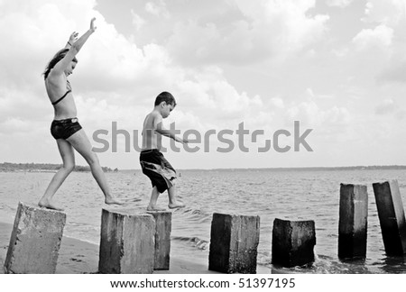 Young kids having fun on pilings at seashore - stock photo