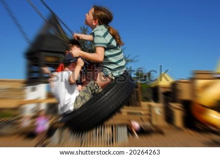 Young kids having fun on tire swing - stock photo