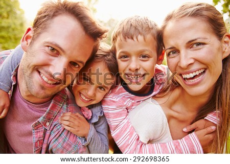 Young kids hugging parents outdoors, close up portrait - stock photo
