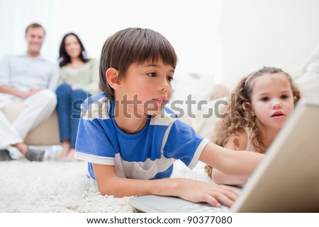 Young kids playing computer games on the carpet with parents behind them - stock photo